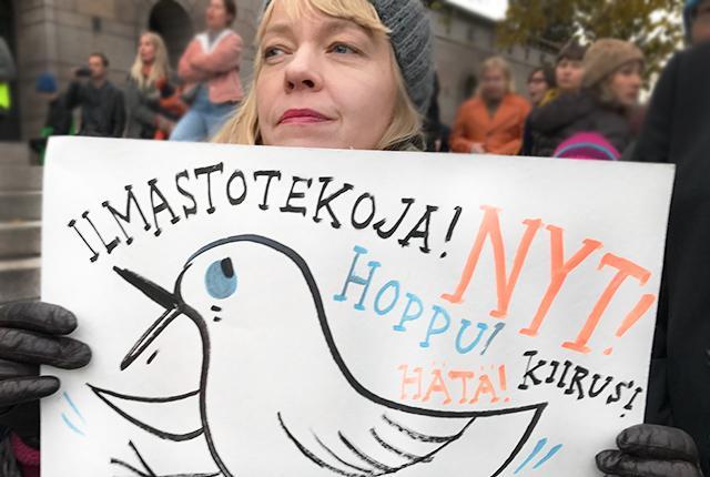 Nainen mielenosoituksessa. Kädessä kyltti, jossa teksti: Ilmastotekoja nyt. Hoppu, hätä, kiire.